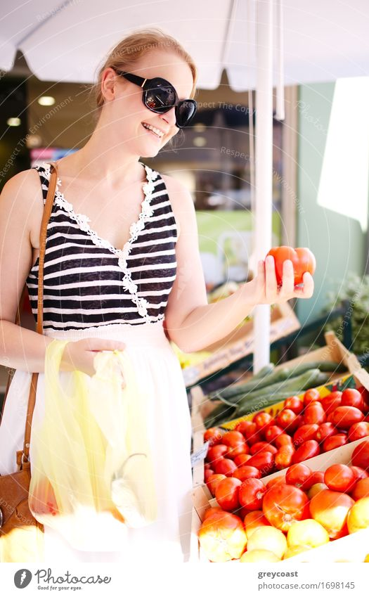 Young woman shopping for fresh tomatoes at an open-air stall choosing items from a row of wooden boxes Vegetable Fruit Apple Grain Shopping Youth (Young adults)