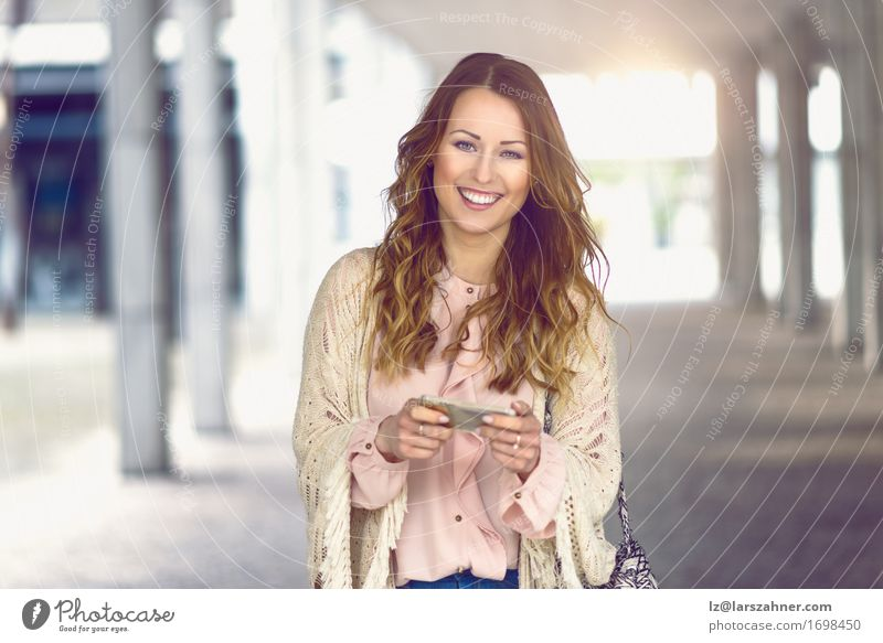 Fashionable woman holding her mobile Human being Woman Vacation & Travel Youth (Young adults) City Beautiful 18 - 30 years Adults Street Feminine Lifestyle Fashion Modern Action Technology Smiling