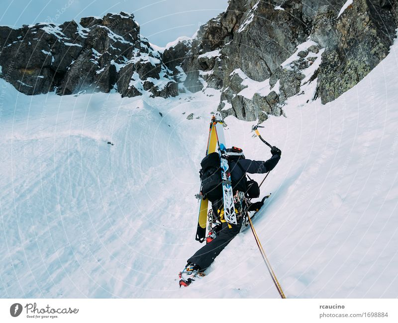 Ice climbing: mountaineer on a mixed route of snow and rock Human being Nature Vacation & Travel Man Landscape Loneliness Winter Black Mountain Adults Cold