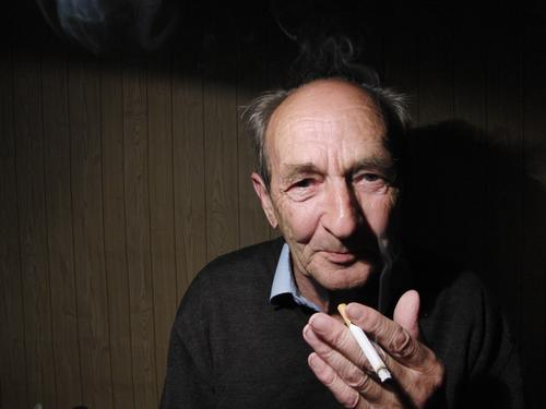 Grandfather smokes. Colour photo Interior shot Copy Space left Neutral Background Shadow Contrast Portrait photograph Looking into the camera Forward Smoking