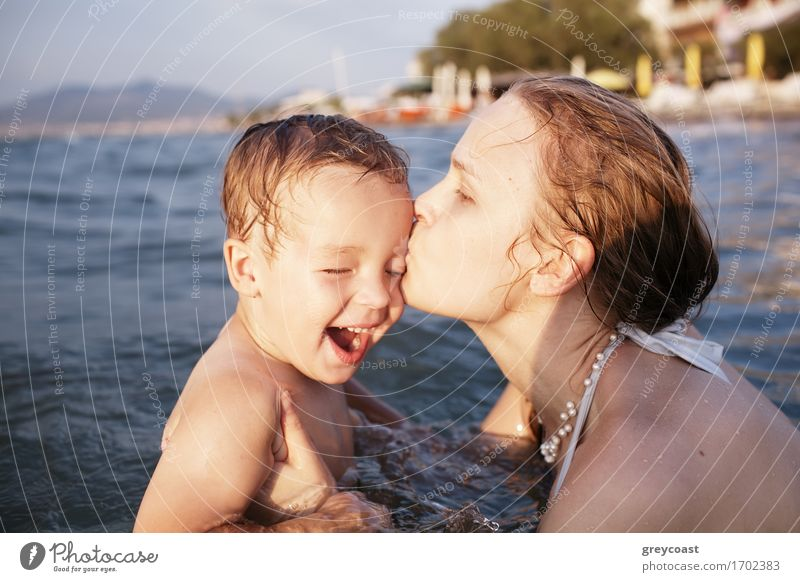 Mother kissing her young child while bathing in the sea waters during sunset Playing Vacation & Travel Sun Beach Ocean Waves Human being Child Boy (child)