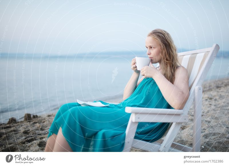 Wide shot of young girl enjoying a cup of tea at the seaside sitting relaxing on a deckchair with a blissful expression overlooking a tropical beach Beverage