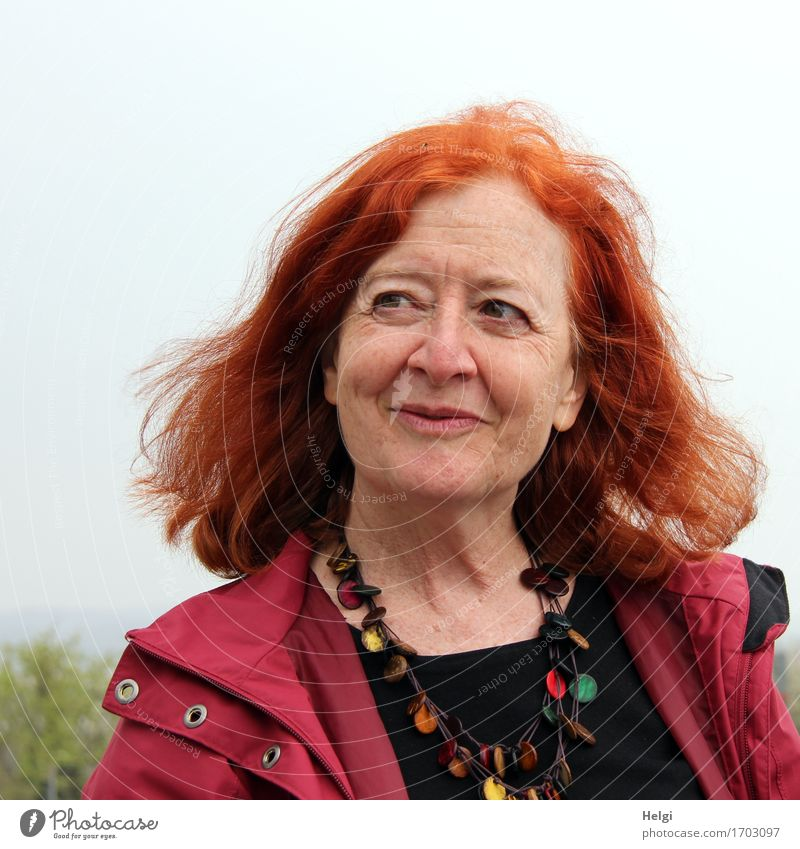 Portrait of an elderly woman with long red hair, looking mischievously to the side, with red jacket, black shirt and colourful necklace Human being Feminine