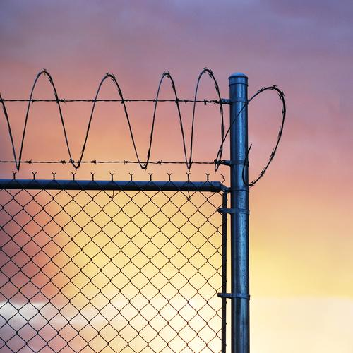 Jail idyll. Metal Threat Captured Penitentiary Barbed wire fence Alcatraz Sunset Diffuse Sky Freedom Rehabilitate Guantanamo Shackled Grating Loneliness Army