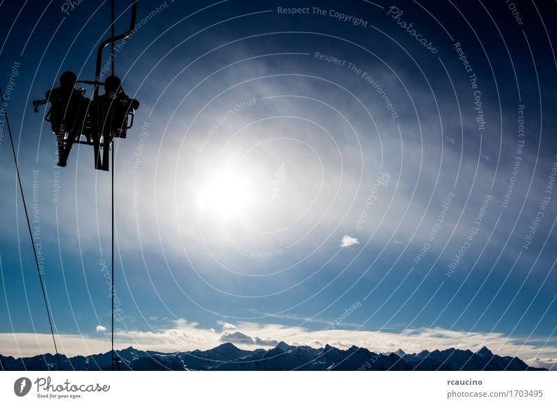 Two skiers in a chairlift backlit by the sun Vacation & Travel Tourism Winter Snow Mountain Chair Sports Skiing Human being Nature Landscape Sky Diet Lift
