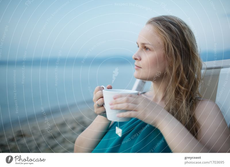 Woman enjoying a cup of tea at the seaside sitting relaxing on a deckchair with a blissful expression overlooking a tropical beach Beverage Drinking Coffee Tea