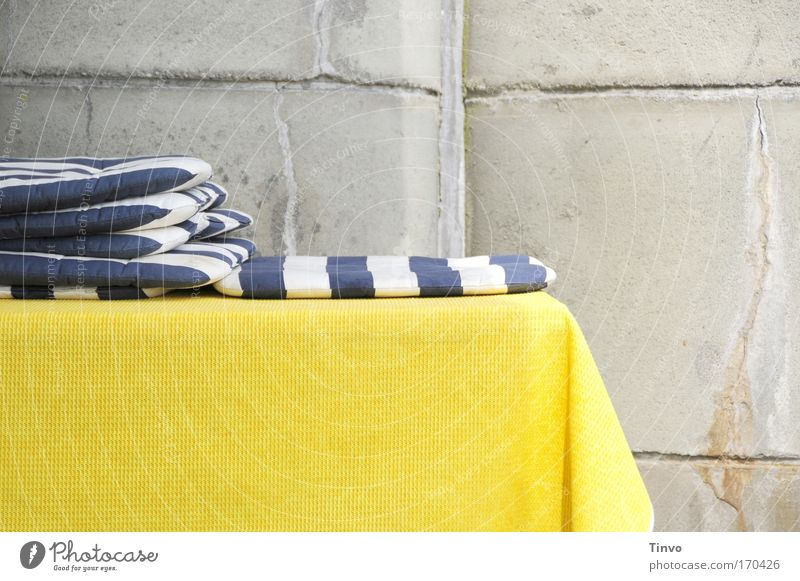 blue-white seat cushions on yellow tablecloth in front of concrete wall Colour photo Multicoloured Exterior shot Close-up Copy Space bottom Day Table Blue
