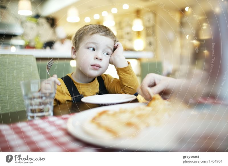 Bored little boy in a restaurant sitting with an empty plate in front of him sitting with his head resting on his hand Nutrition Eating Lunch Dinner Diet Plate