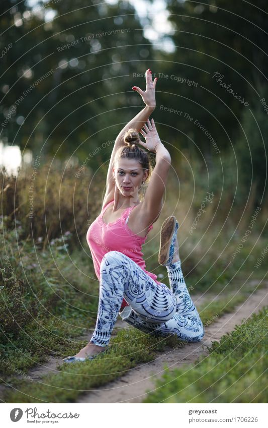 Supple graceful young woman exercising outdoors on a rural track posing on one knee with her hands held above her head Diet Lifestyle Beautiful Body Relaxation