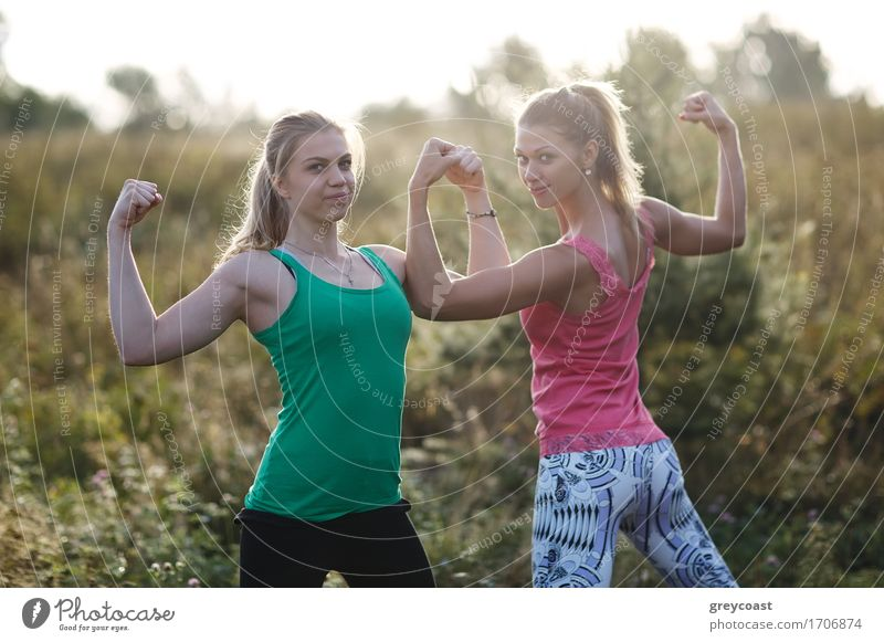 Two athletic girls flexing their arm muscles Human being Woman Youth (Young adults) Summer Young woman Girl 18 - 30 years Adults Funny Sports Garden Park Blonde