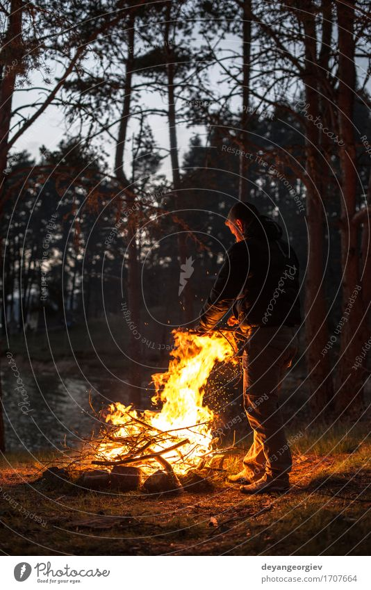 Man lights a fire in the fireplace Leisure and hobbies Vacation & Travel Tourism Adventure Camping Summer Mountain Hiking Human being Adults Nature Warmth Tree