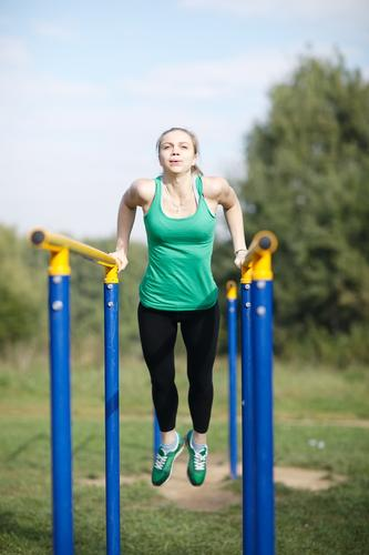 Attractive fit young woman gymnast exercising outdoors on parallel bars during a training workout Sports Fitness Sports Training Young woman