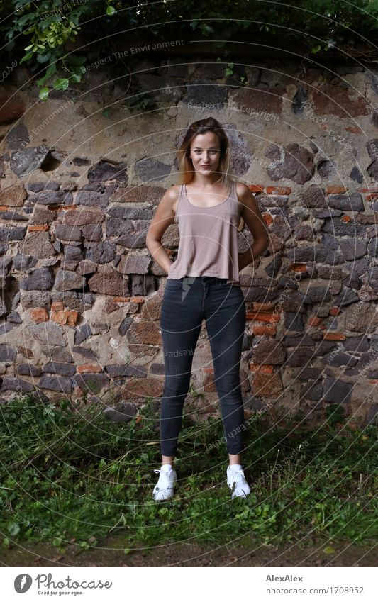 Attracted Joy Beautiful Athletic Young woman Youth (Young adults) 18 - 30 years Adults Landscape Ivy Wall (barrier) Wall (building) Jeans Top Sneakers Blonde