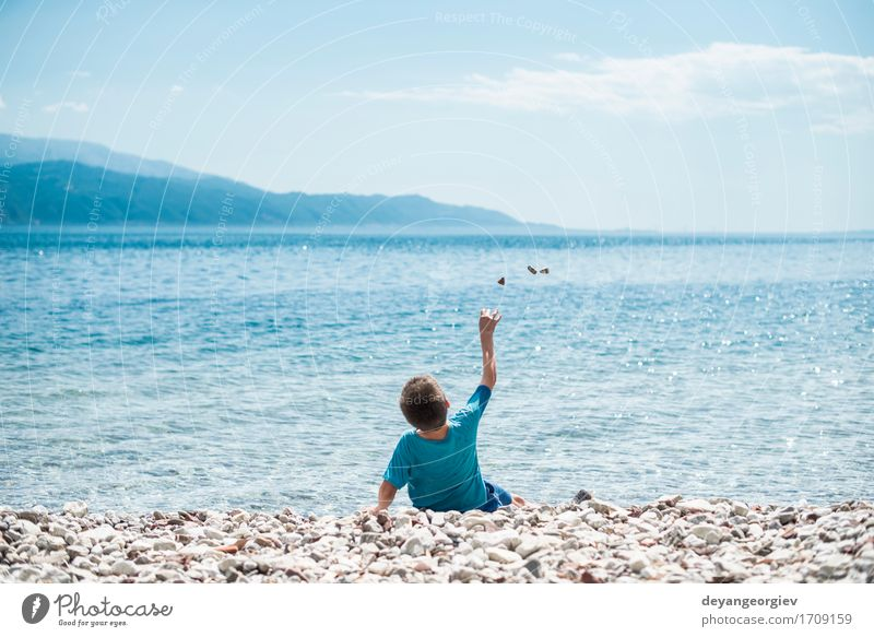 Children throw stones at the wate Human being Nature Vacation & Travel Blue Summer Beautiful Ocean Girl Beach Lifestyle Boy (child) Playing Small Stone Rock
