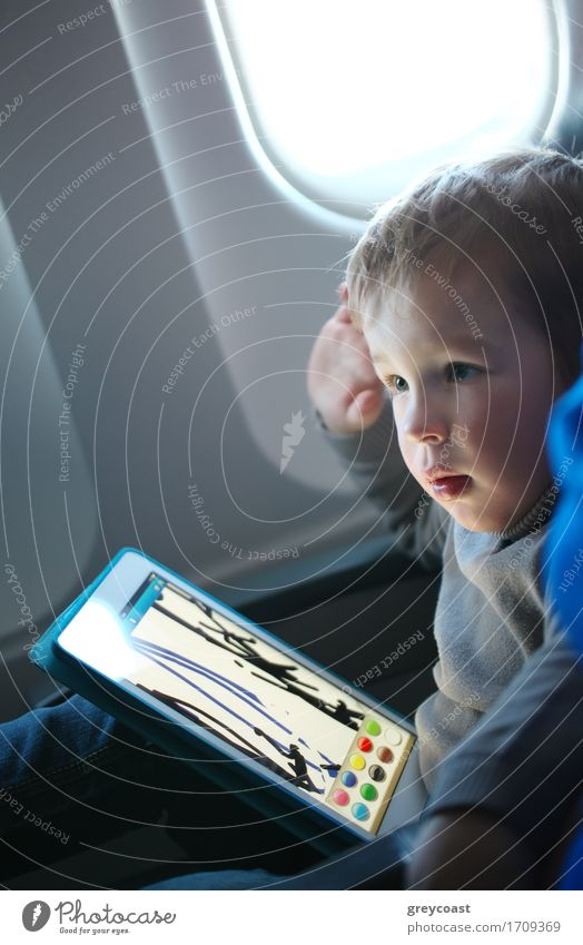 Little boy sitting in his seat during a flight and painting on a tablet computer in an airplane Leisure and hobbies Playing Computer games Vacation & Travel