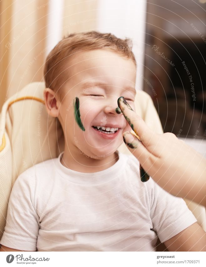 Little boy laughing as his mother paints his face streaking his cheek and dabbing his nose with black face paint Joy Happy Leisure and hobbies Playing Child