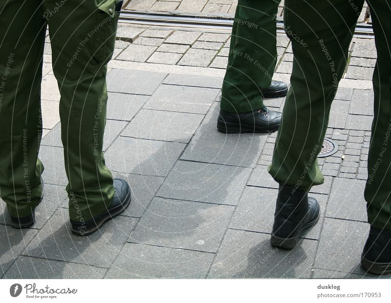 police Colour photo Exterior shot Downward Human being Legs Feet Workwear Work and employment Observe Fight Threat Police Force Protection Green Pants Guard