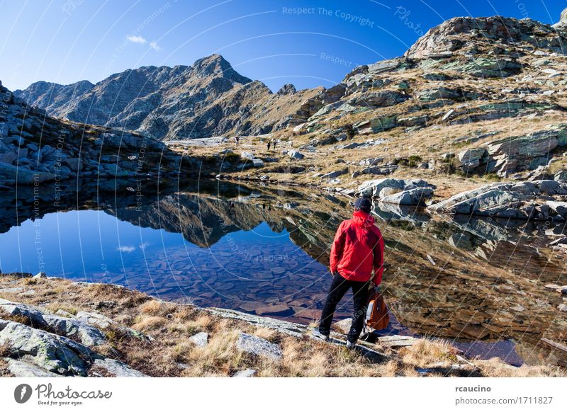 Male hiker near a small mountain lake. Human being Sky Nature Vacation & Travel Man Summer Landscape Red Loneliness Mountain Adults Lanes & trails Autumn Sports