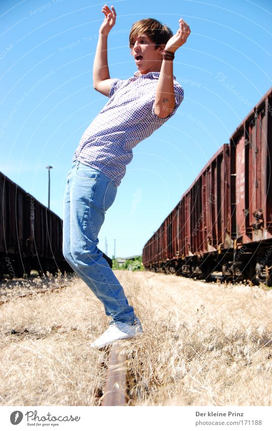 The astonished young man in front of old goods wagons Copy Space bottom Sunlight Full-length Joy Young man Youth (Young adults) 1 Human being Freight train