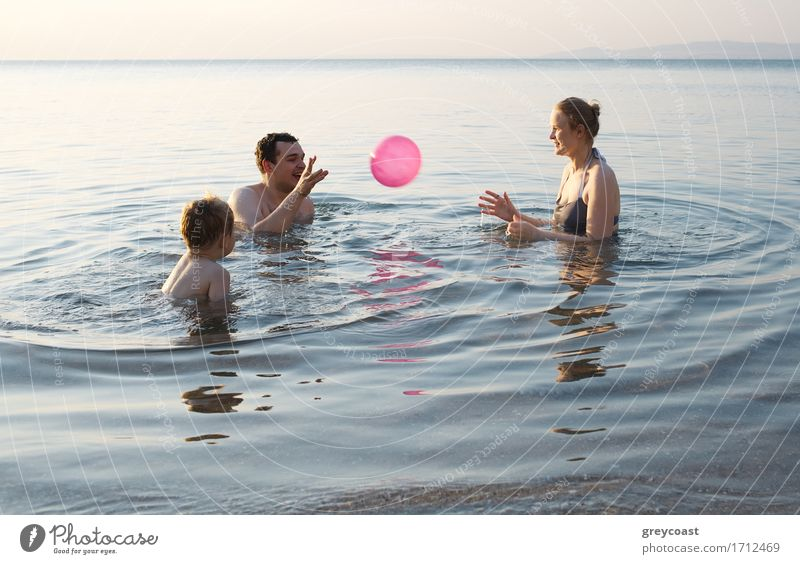 Young family enjoying the sea at sunset paddling in the shallows together playing with the ball as they enjoy their summer vacation Joy Happy