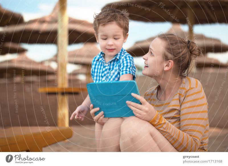 Little boy with his mother at a beach resort playing with a tablet computer on the beach under straw beach umbrellas Joy Happy Playing Vacation & Travel Beach