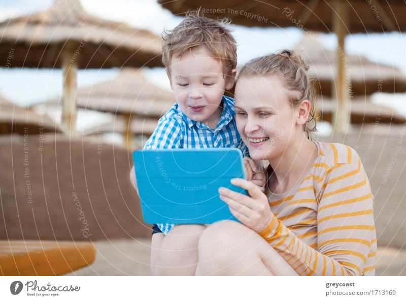 Happy mother and her small son at a beach resort playing on a tablet computer together under beach umbrellas at the seaside Joy Playing Beach Entertainment