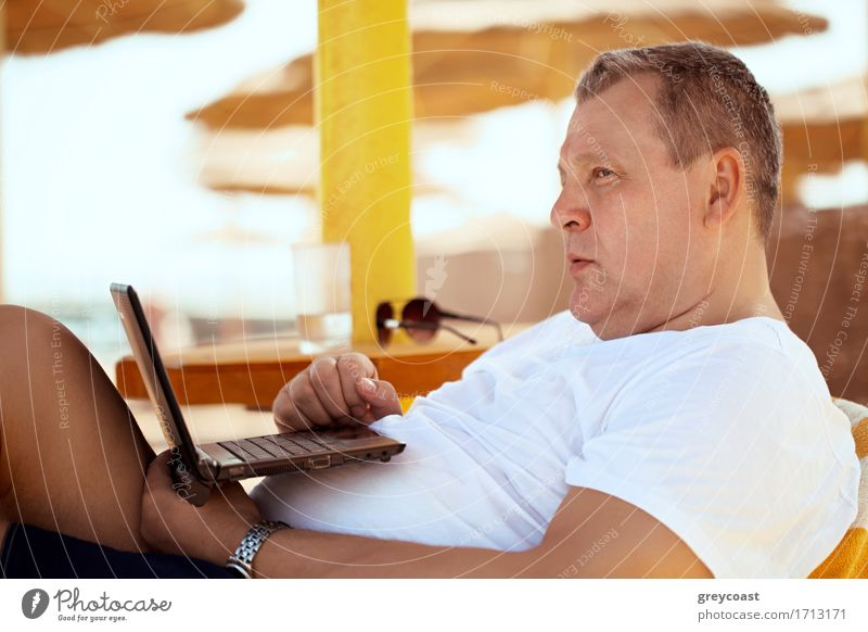 Man relaxing with a laptop at a beach resort reclining on a comfortable chair under a straw beach umbrella staring thoughtfully into the distance, side view