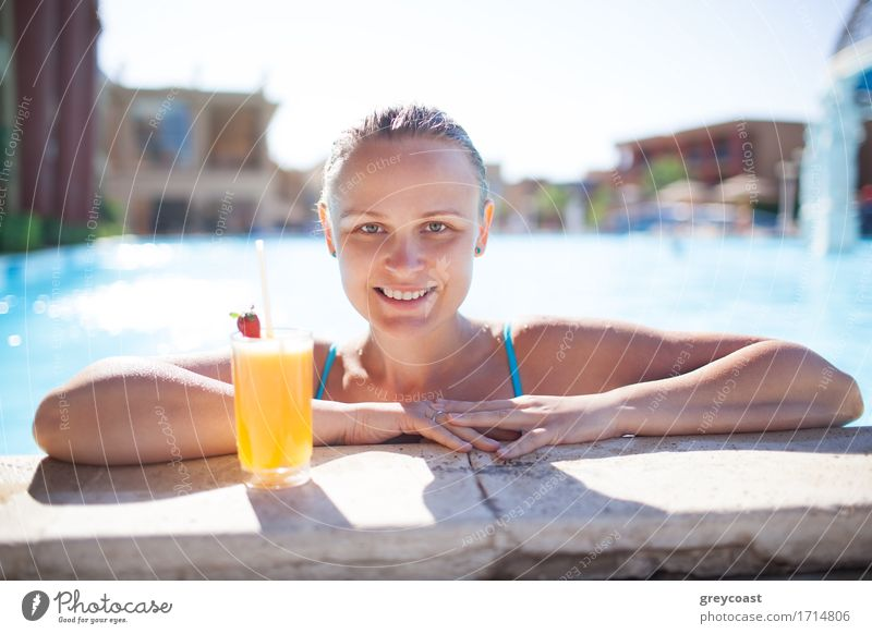 Smiling young woman enjoying a refreshing orange drink or cocktail in the pool resting her arms on the pool surround smiling at the camera Beverage Drinking