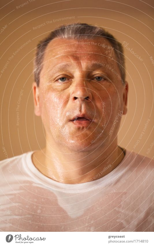 Tired looking hot perspiring middle-aged man after a workout, closeup head and shoulders portrait looking directly at the camera Face Health care Wellness