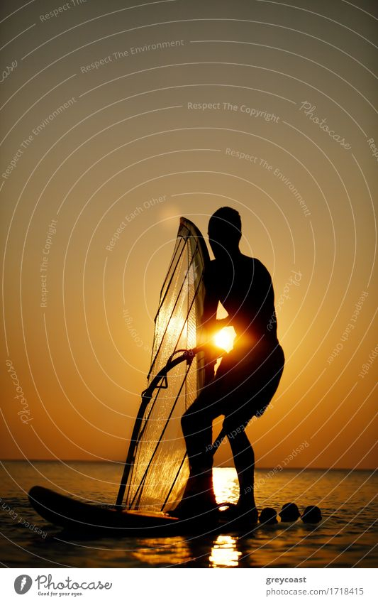 Man sailboarding at sunset silhouetted against the bright orb of the sun in a colorful orange sky on a calm ocean Relaxation Vacation & Travel Freedom Summer