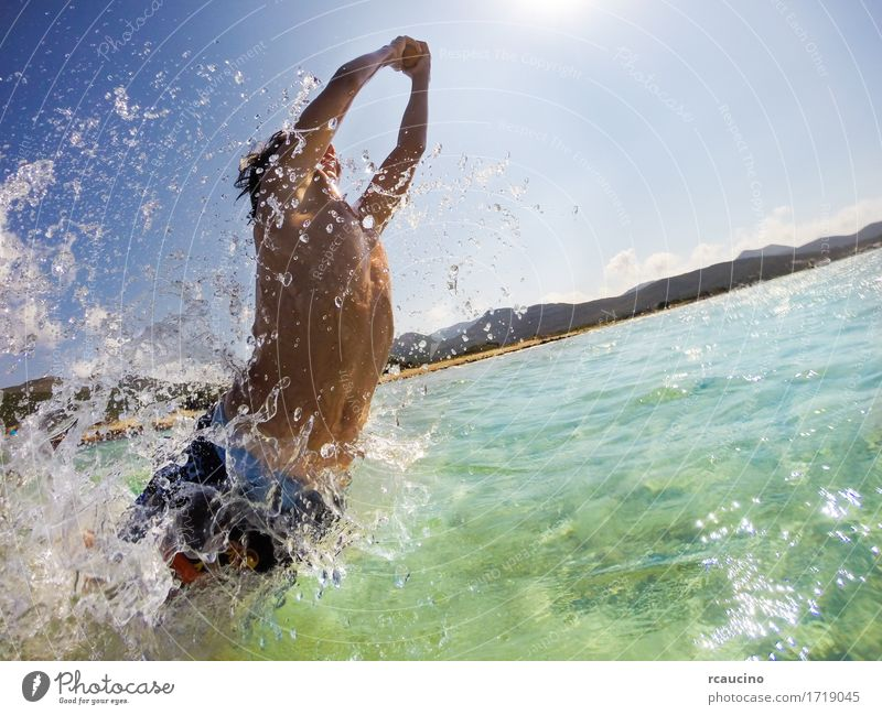 Boy jumping in water, playing and having fun Human being Child Sky Nature Vacation & Travel Man Blue Summer White Sun Ocean Joy Beach Adults Sports Coast