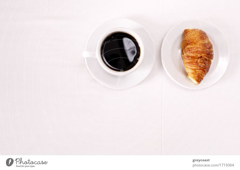 Overhead view of a cup of black espresso coffee and a freshly baked croissant for breakfast. High angle close up Bread Croissant Jam Breakfast Coffee Espresso