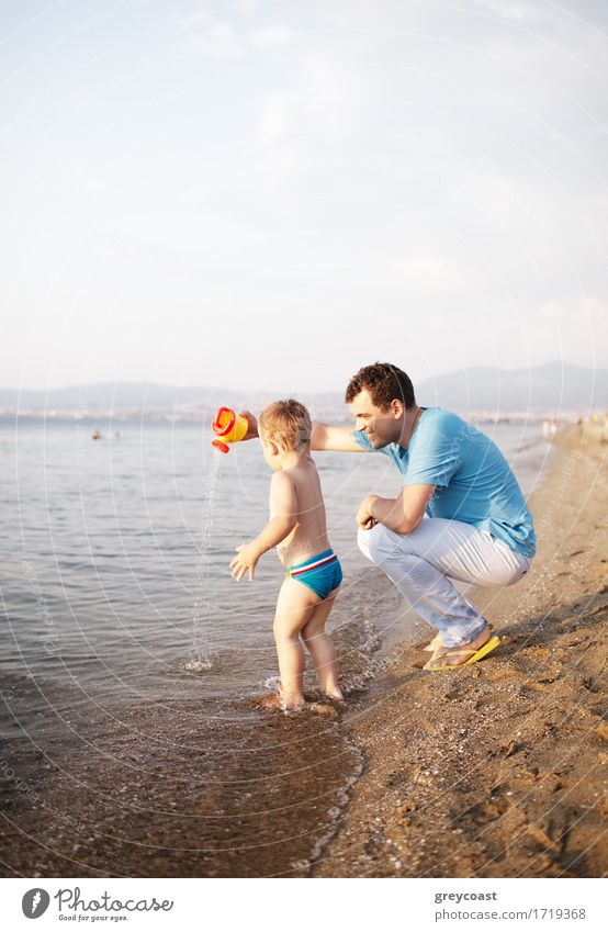 Young father playing with his son at the beach crouching down a the edge of the water as the toddler happily paddles in the shallow water playing with a watering can