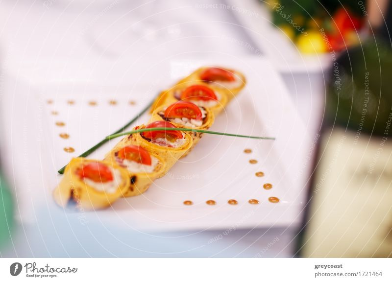 Gourmet appetizers beautifully plated at an upmarket restaurant arranged in a diagonal row on a contemporary square plate and garnished with chives. Shallow dof
