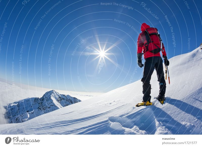 Mountaineer at the top of a snowy mountain Sky Nature Man Blue Sun Landscape Red Loneliness Winter Adults Sports Snow Power Success Stand