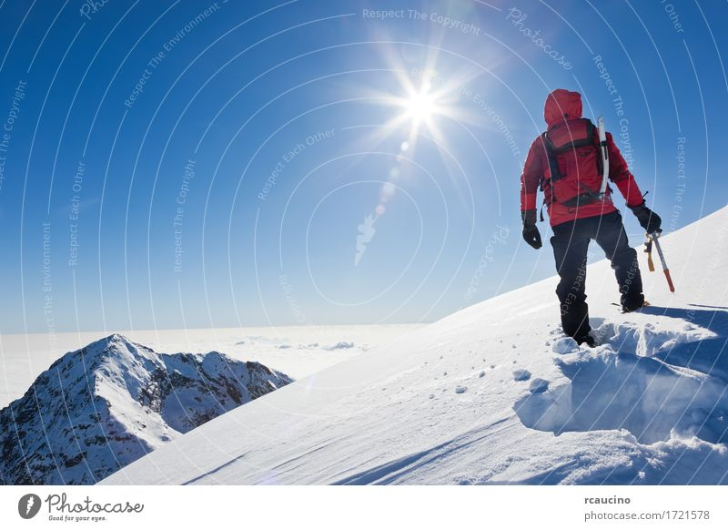 Mountaineer reaches the top of a snowy mountain Sky Nature Man Blue Sun Landscape Red Loneliness Winter Adults Sports Snow Power Success Stand