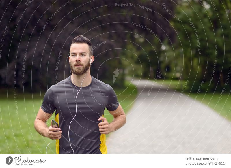 Fit young man jogging in a park Lifestyle Body Face Music Sports Jogging Man Adults 1 Human being 18 - 30 years Youth (Young adults) Fitness Listening Action