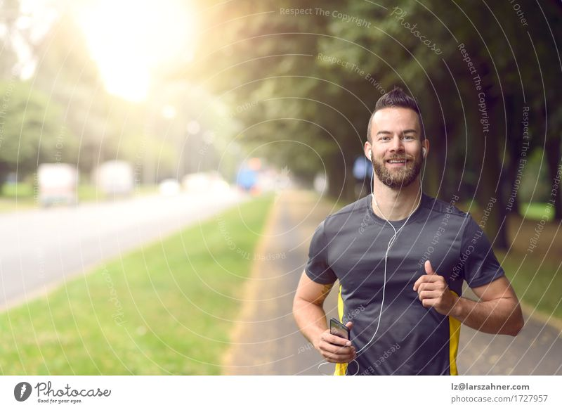 Man jogging along a tree lined sidewalk Lifestyle Happy Body Face Music Sports Jogging Masculine Adults 1 Human being 18 - 30 years Youth (Young adults) Fitness