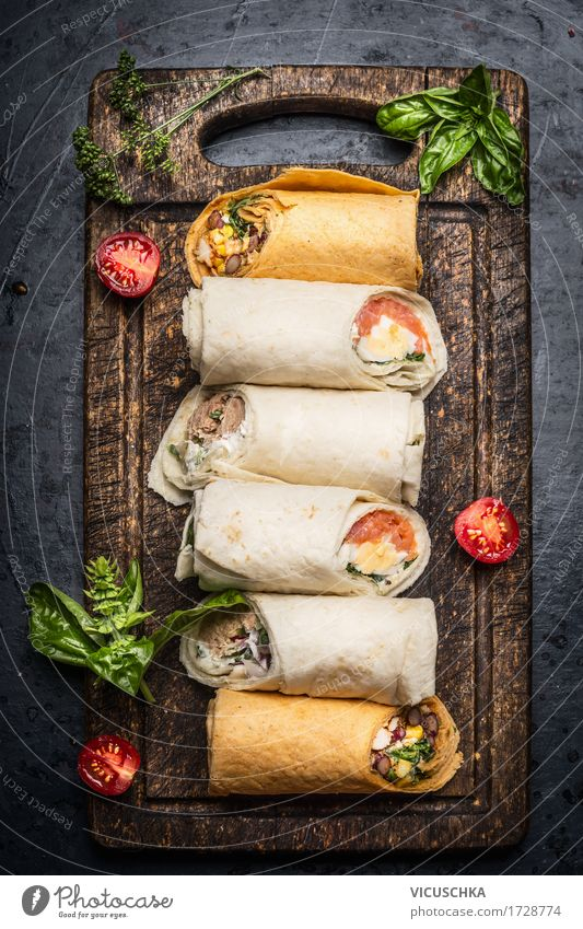 Various tasty tortilla wraps on rustic chopping board Food Vegetable Lettuce Salad Herbs and spices Nutrition Lunch Dinner Buffet Brunch Organic produce Diet