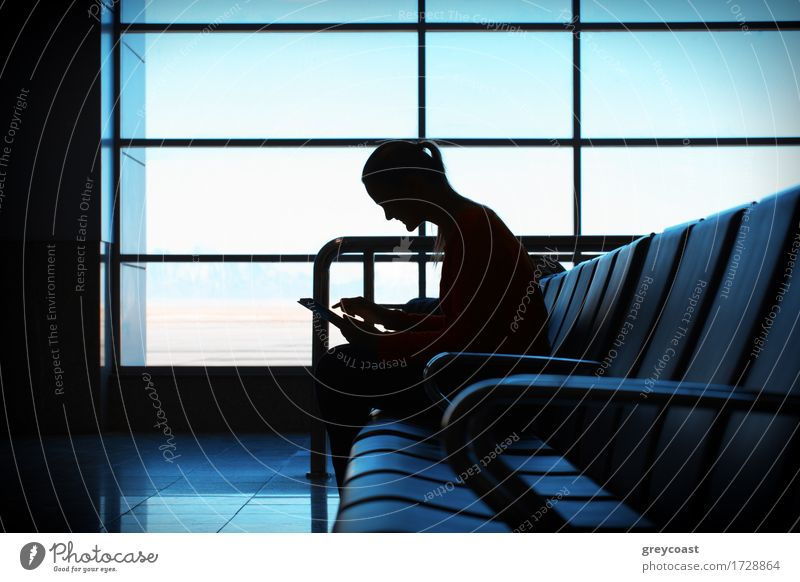 Woman in the aiport lounge sitting in chair by the window and using a tablet computer for checking her flight details with wifi connection. Silhouette Happy