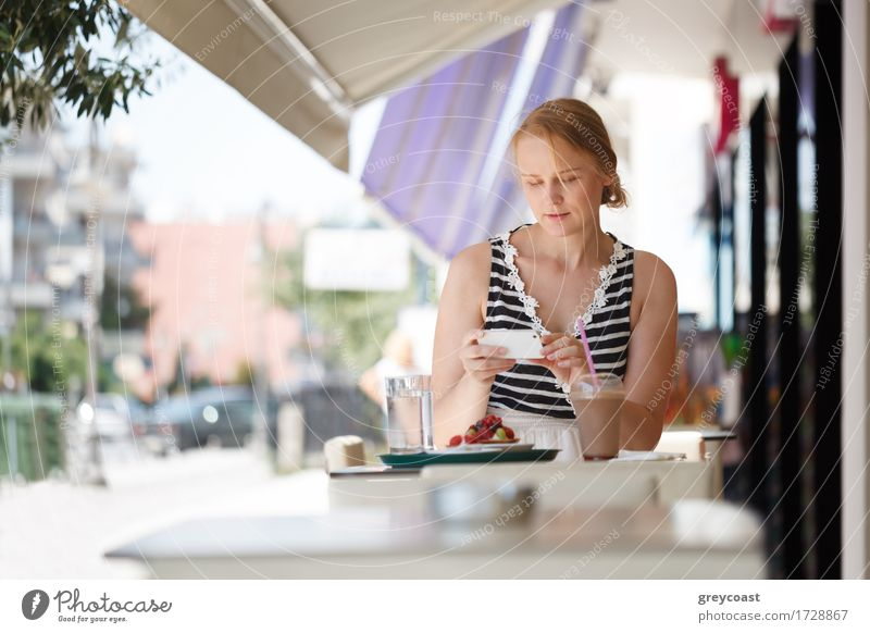 Young woman using her smartphone sitting in outdoor cafe Lunch Dinner Summer Telephone PDA Human being Girl Youth (Young adults) 1 18 - 30 years Adults Blonde