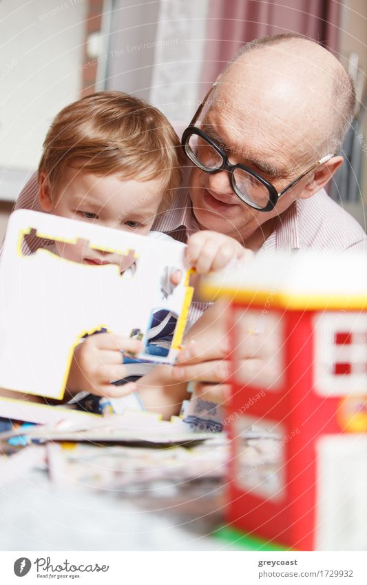 Grandfather helping his little grandson to solve puzzle. Happy family time Joy Leisure and hobbies Playing Child Human being Boy (child) Man Adults