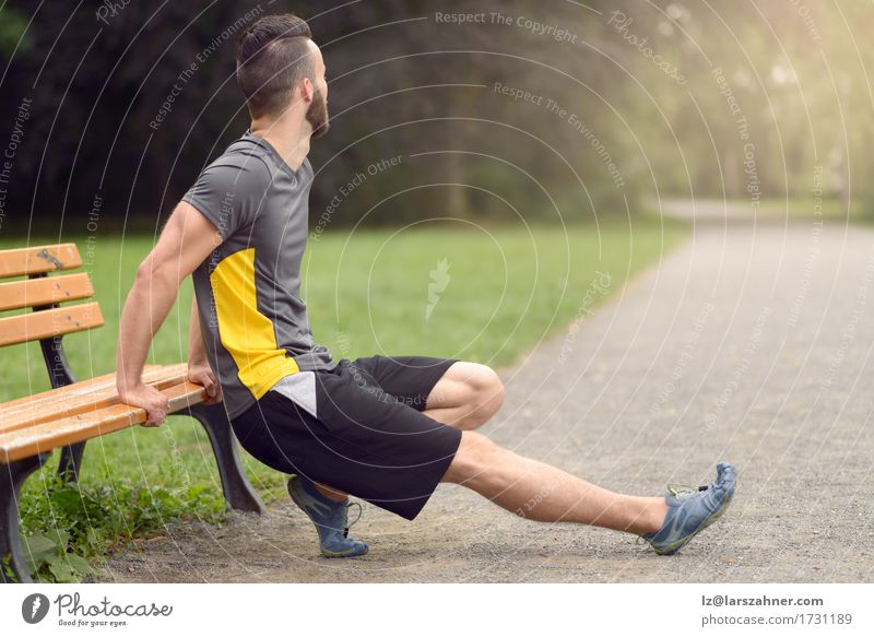 Young man stretching in a park Lifestyle Body Sports Masculine Man Adults 1 Human being 18 - 30 years Youth (Young adults) Park Fitness Action Anonymous Bench