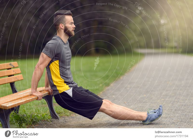 Young man exercising in a park Lifestyle Body Sports Man Adults 1 Human being Nature Park Beard Wood Fitness Athletic Modern Action Balance bearded Bench