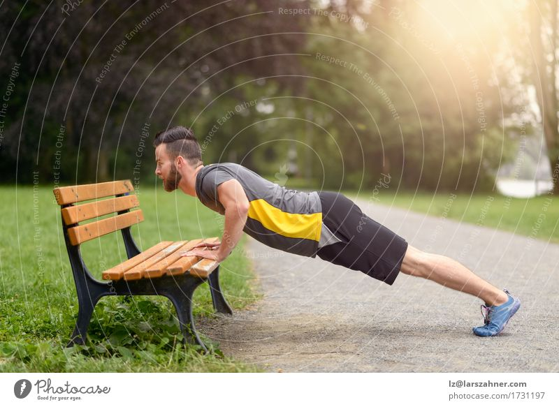 Young man doing push-ups in a park Lifestyle Body Face Sports Masculine Man Adults 1 Human being 18 - 30 years Youth (Young adults) Park Beard Fitness Action