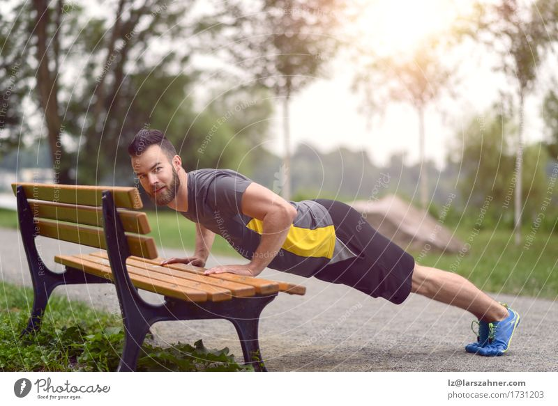 Young man working out doing push-ups on a wooden park bench Lifestyle Body Face Sports Man Adults 1 Human being 18 - 30 years Youth (Young adults) Park Beard