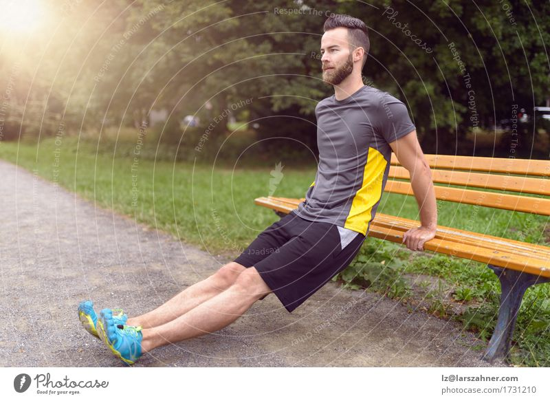 Young man exercising in a park Human being Nature Man Adults Sports Lifestyle Wood Park Copy Space Body Modern Action Fitness Bench Athletic Balance