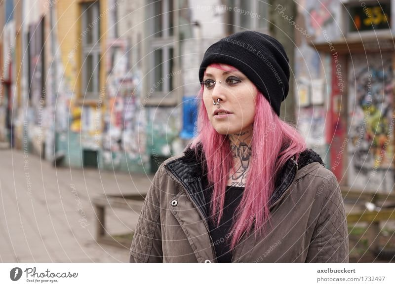 pierced and tattooed woman in front of graffiti covered building Human being Woman Youth (Young adults) City Young woman Loneliness 18 - 30 years Adults Sadness