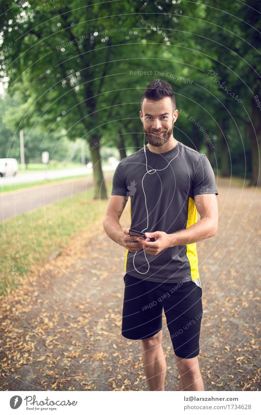 Attractive bearded man listening to music Lifestyle Face Summer Music Sports Telephone PDA Man Adults 1 Human being 18 - 30 years Youth (Young adults) Park