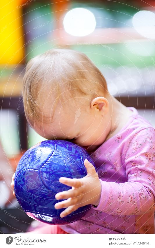 Cute little baby playing with a big blue ball sitting with its face pressed up against the ball, side view Joy Playing Summer Child Baby Girl Infancy 1